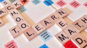 Scrabble board with block tiles spelling Learn, Read, Math, Back to School